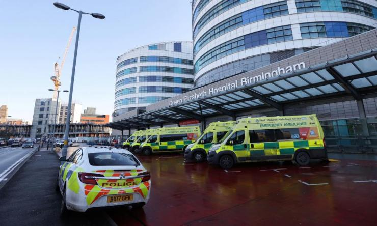 Ambulances and a police car are seen outside the Queen Elizabeth Hospital Birmingham on New Year's eve.