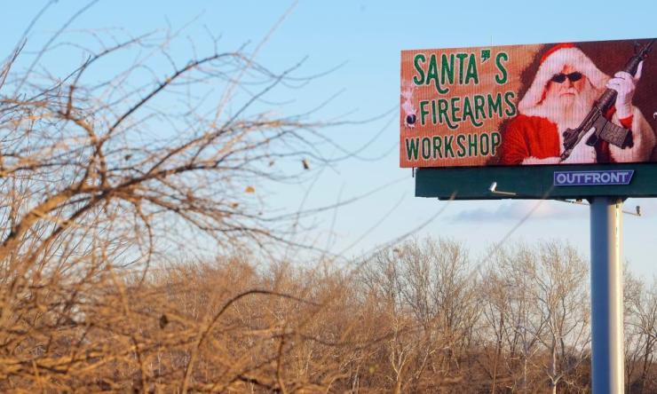 A digital billboard advertises a gun shop located in Easton, Pennsylvania.