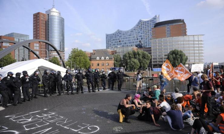 Demonstrators face policemen during a protest next to the Elbphilharmonie.
