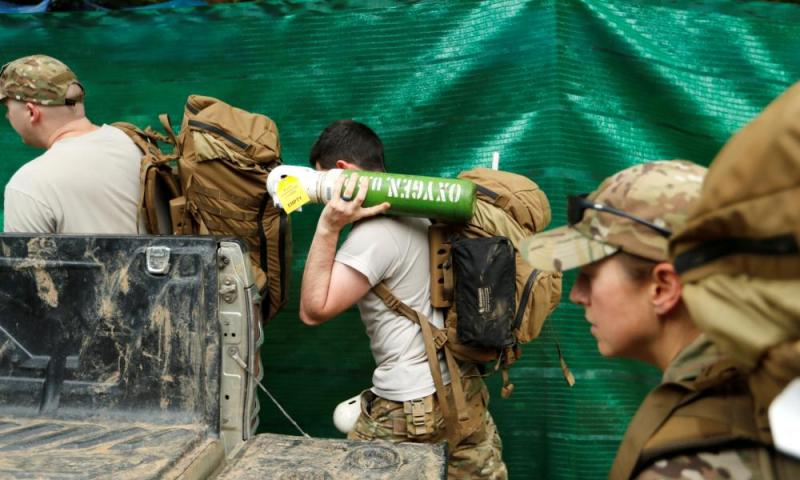 A US military personnel carries an oxygen cylinder at the Tham Luang cave complex