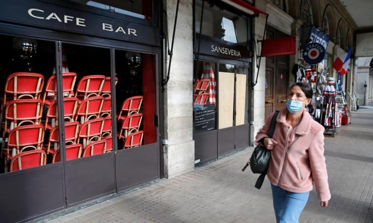A woman wearing a protective face mask walks past a closed cafe at a nearly empty Rue de Rivoli on October 15, 2020 in Paris, France.