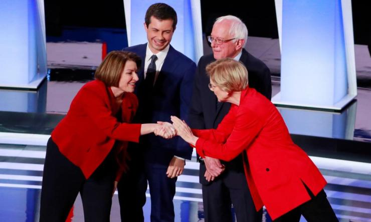 Amy Klobuchar (left) and Elizabeth Warren (right) greet each other at the start of the Democratic debate in Detroit. Pete Buttigieg and Bernie Sanders look on.