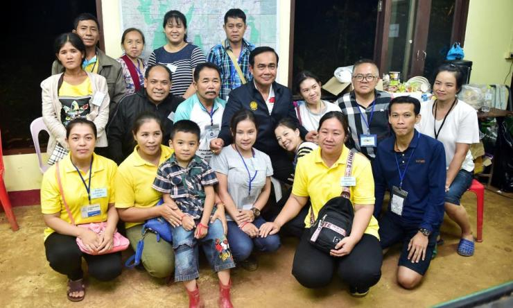 Thailand's Prime Minister Prayuth Chan-ocha poses with relatives of boys trapped in the flooded Tham Luang cave