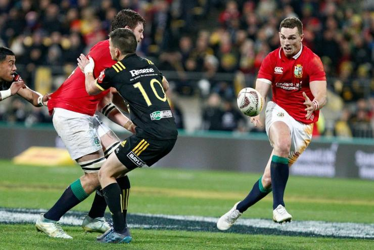 Iain Henderson, left, offloads to George North as he is tackled by Otere Black of the Hurricanes, centre.