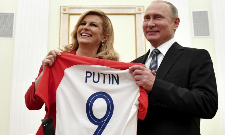 Croatian President Kolinda Grabar Kitarovic (left) presents a shirt to Russian President Vladimir Putin.