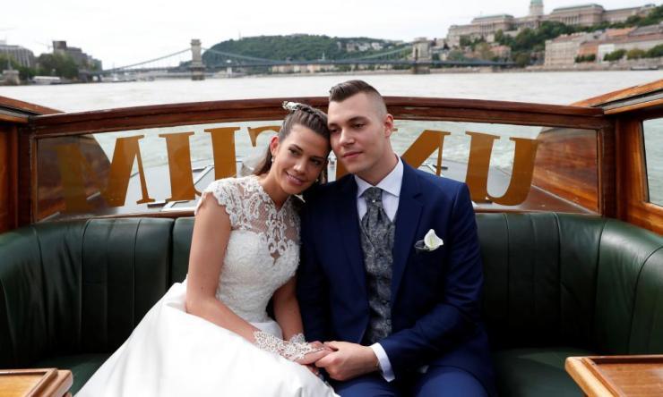 Tokacs-Mathe and Aszalos pose during their wedding photoshoot on a water limousine on the Danube