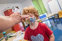 Copil controlat cu termometrul pentru coronavirus