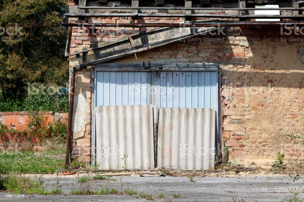 https www istockphoto com photo abandoned red brick garage with metal doors surrounded with rusted gutter and wooden gm1086713318 291563095