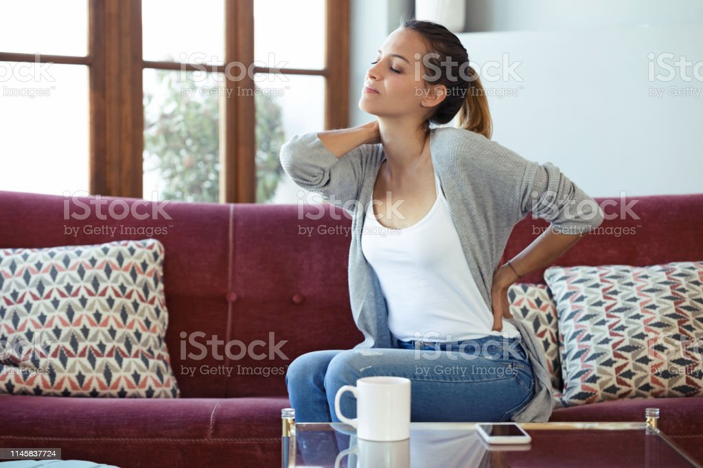 beautiful young woman suffering from back pain while sitting on sofa at home stock photo download image now istock