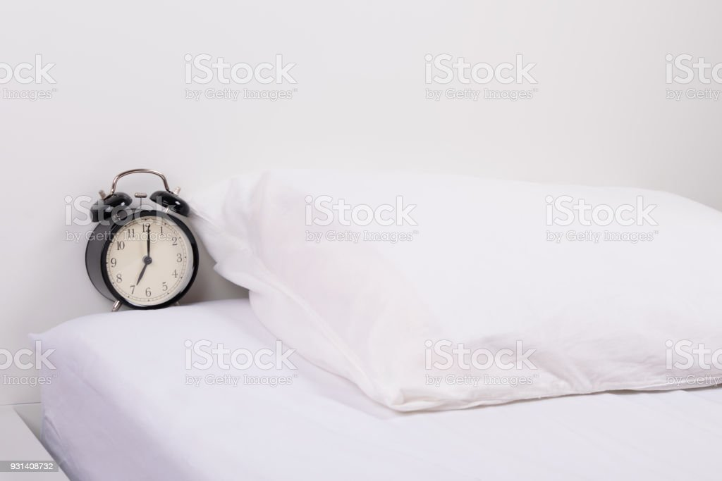 black alarm clock on a white bed background next to a pillow stock photo download image now istock