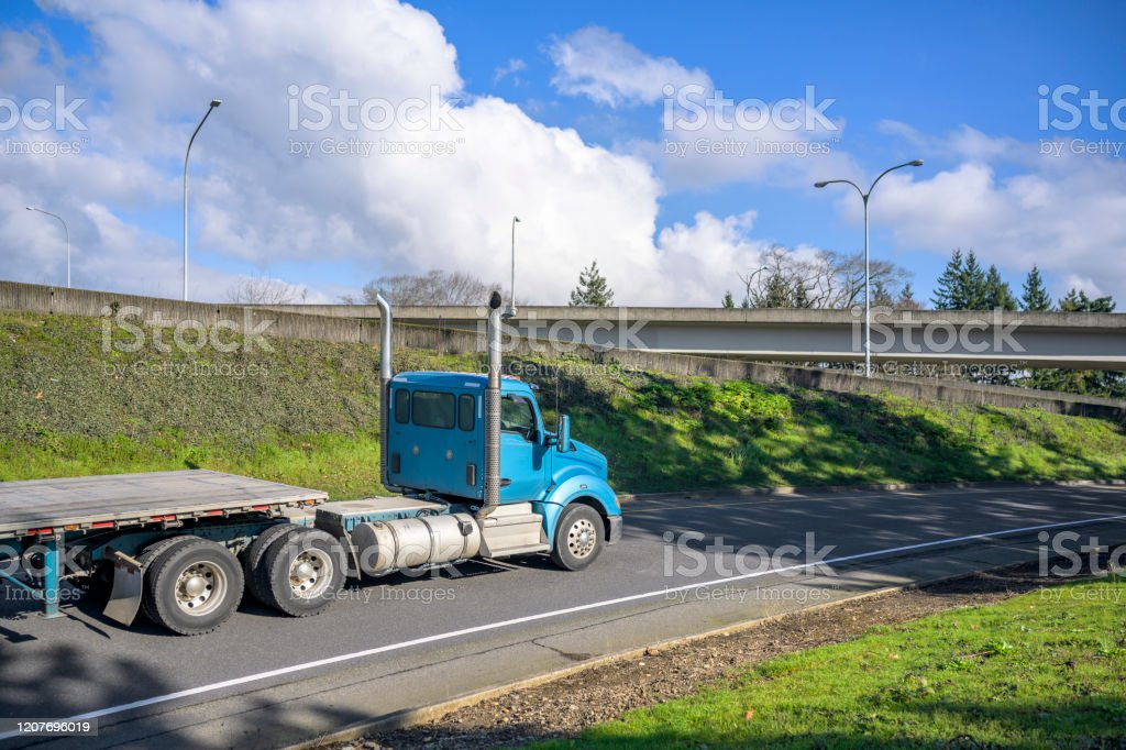 https www istockphoto com photo blue big rig day cab semi truck with vertical exhaust pipes transporting empty flat gm1207696019 348790059