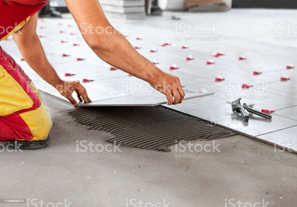 ceramic tiles tiler placing ceramic wall tile in position over adhesive with lash tile leveling system stock photo download image now istock