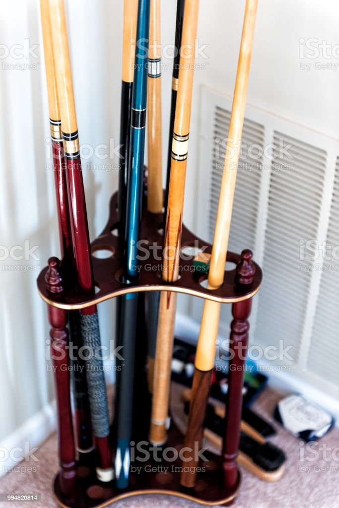 closeup of wooden mahogany finish billiard pool cue sticks standing stand rack holder in living room home with chalk brush cues stock photo download image now istock