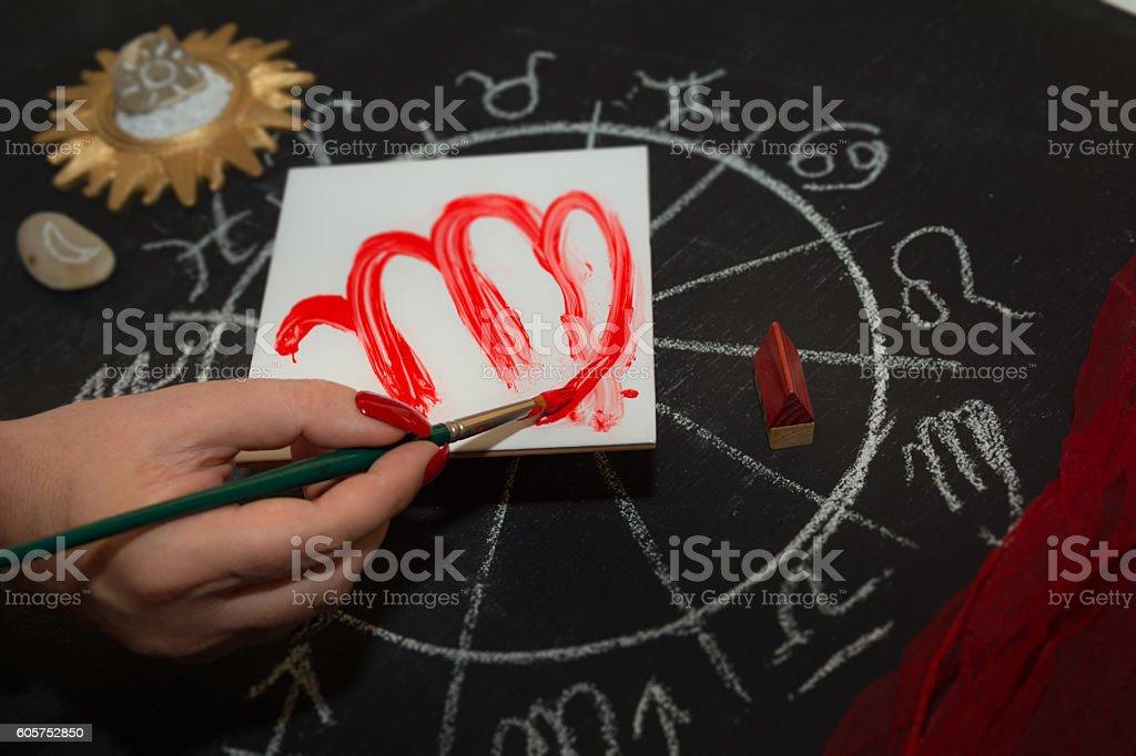 https www istockphoto com de foto female astrologer draws virgo zodiac sign on white tile gm605752850 103849053