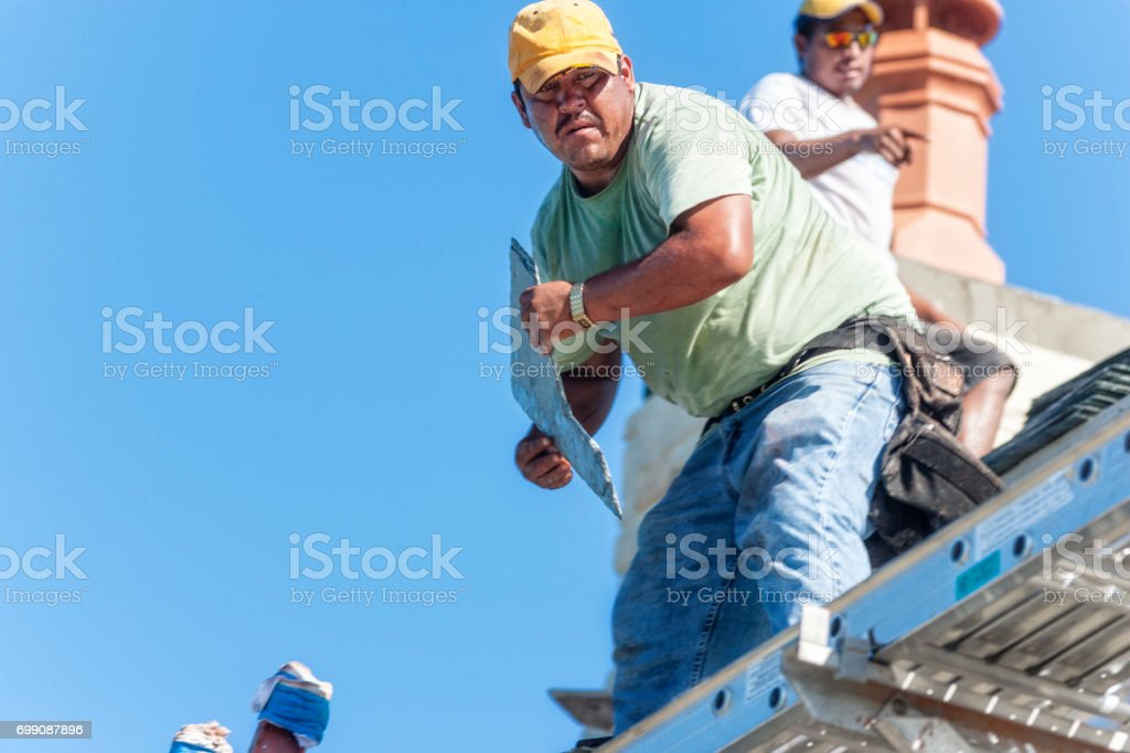 https www istockphoto com photo hispanic roofer looks up after cutting a piece of slate tile while on a roof gm699087896 129541931