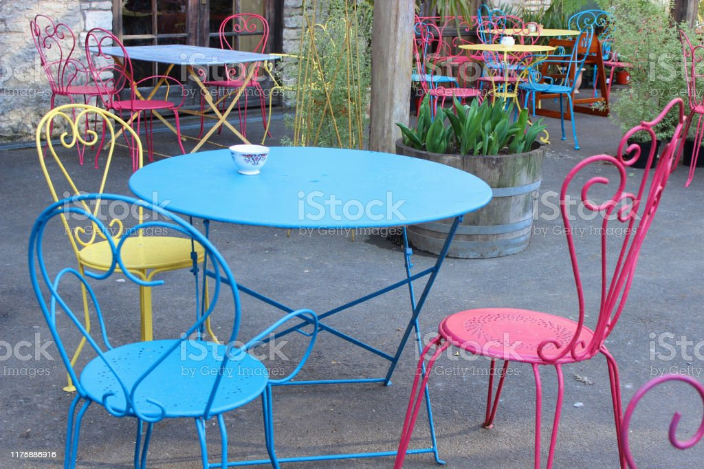 image of coloured painted circular and square metal garden patio tables and chairs in bright colours with rainbow paint yellow pink and turquoise blue mismatched sets for dining eating outside stock photo