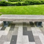 Image Of Modern Garden Bench With Metal Legs And Wooden Seating Top Made From Teak Timber Planks Contemporary Garden Design With Lush Green Lawn Grass And Black Grey And White Brick Paving