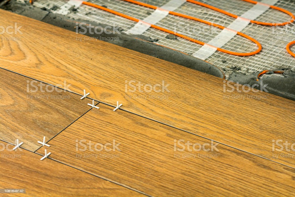 https www istockphoto com photo installation of ceramic tiles and heating elements in warm tile floor renovation and gm1081649142 290060548