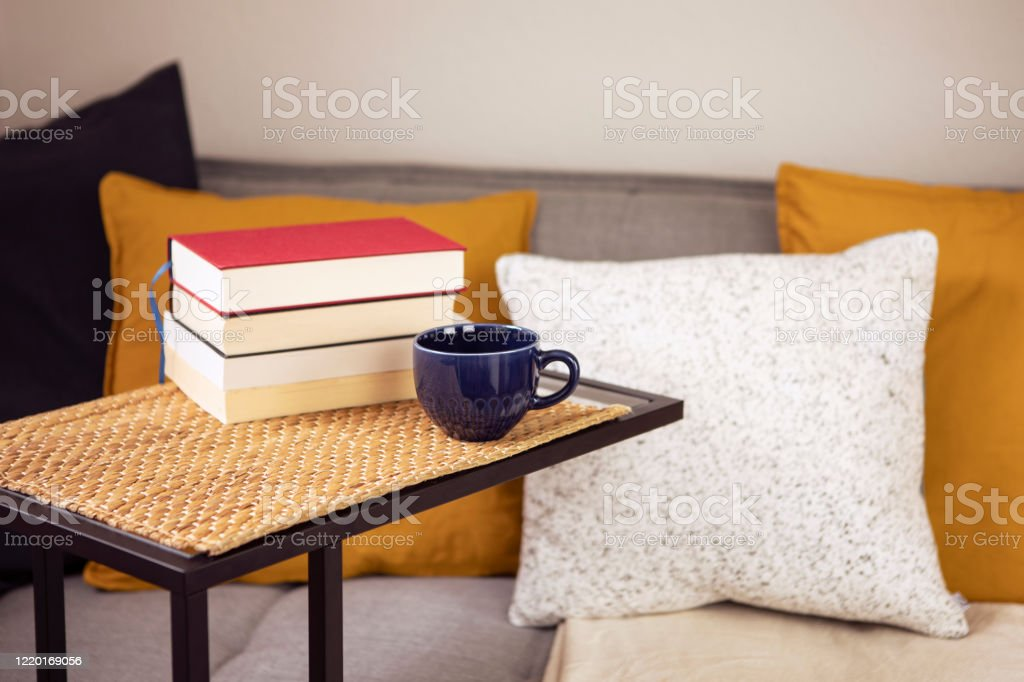 https www istockphoto com photo interior with books on the table cup of coffee or tea with cozy sofa with cushions gm1220169056 357177679