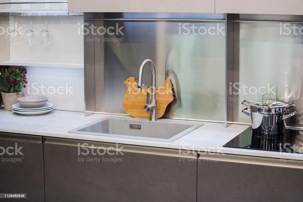 https www istockphoto com photo kitchen faucet modern gray kitchen in loft style white table luxury faucet kitchen gm1129462649 298370951