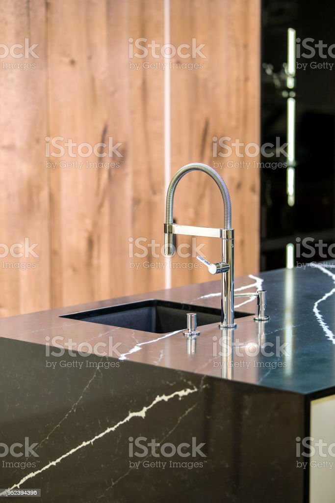 https www istockphoto com photo kitchen faucet modern kitchen in loft style black marble table wooden luxury kitchen gm952394396 260002199
