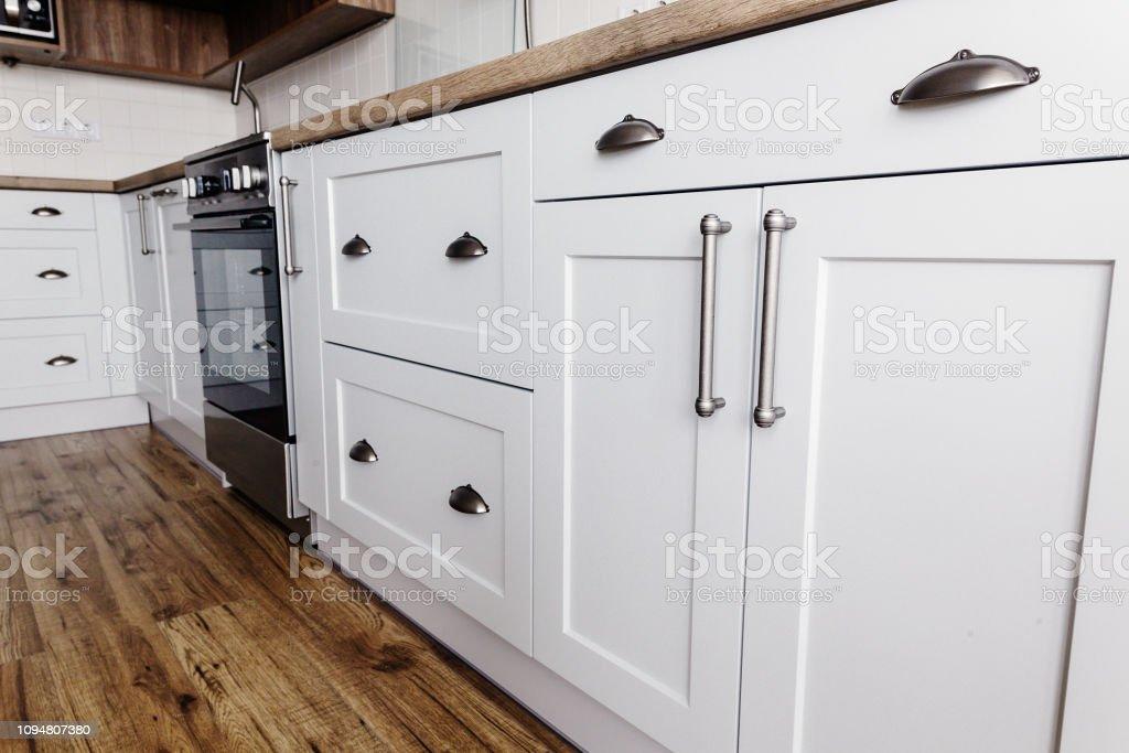 photo libre de droit de meubles de cuisine moderne de luxe de couleur grise et poignee en acier four evier table en bois et plancher gris armoires de style scandinave renovation residentielle