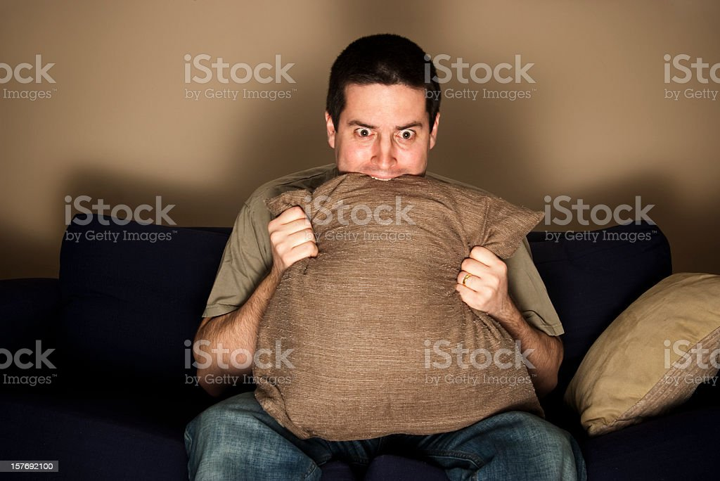 https www istockphoto com photo man bites pillow in fear while watching tv gm157692100 10201494