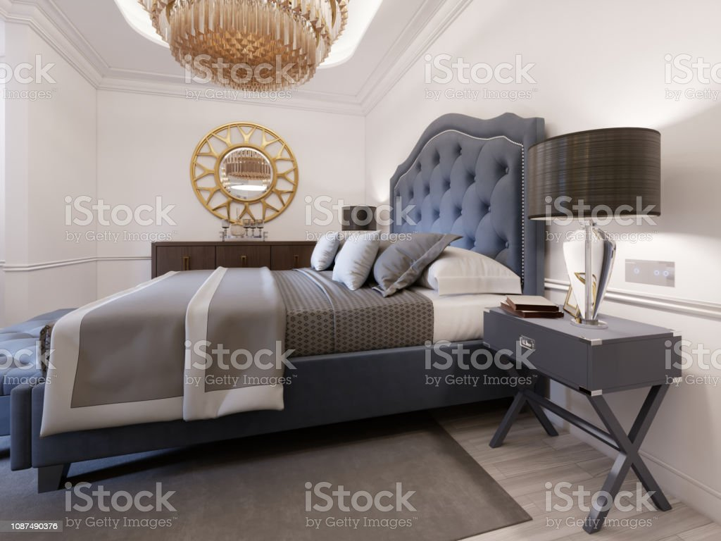 Modern Bed In Classic Blue Style With Bedside Table And Lamp Large Glass Chandelier Over A Dresser With A Decor And A Golden Mirror Above Modern Bedroom Stock Photo Download Image