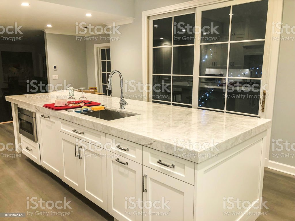 modern white kitchen with marble countertop and porcelain tile floor looks like wood floor stock photo download image now istock