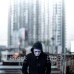 Mystery Hoodie Man In White Mask Standing In The Rain On Rooftop Of Abandoned Building Bipolar Disorder Or Major Depressive Disorder Depression Concept Stock Photo Download Image Now Istock
