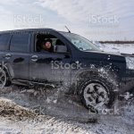 Offroad Crossover Nissan Xtrail 4x4 Quickly Goes Lifting Snow In Winter With A Cheerful Woman Passenger Looking Out The Open Window Stock Photo Download Image Now Istock