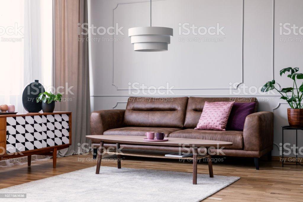 https www istockphoto com fr photo vraie photo de salon gris clair int c3 a9rieur avec fen c3 aatre avec rideaux sofa en cuir gm1027582636 275495716