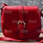 Red Leather Bag On A Wooden Shelf Against A Gray Concrete