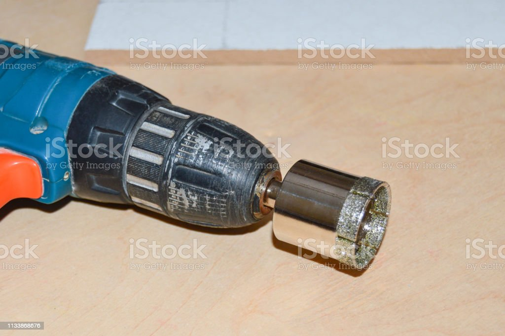screwdriver with diamond tile drill bit and ceramic tile in wooden table close up stock photo download image now istock