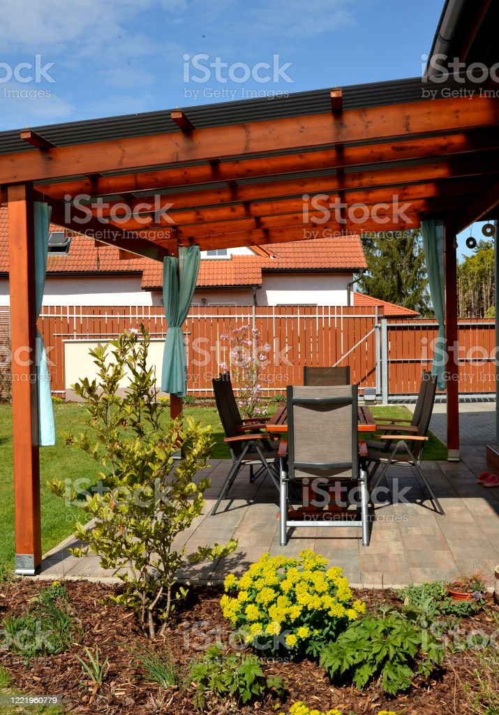 spring flowers at the terrace with furniture table blooming around blooming perennials wooden structure with roofing pergola with turquoise curtains yellow brown wooden tiles sun at the house textile stock photo