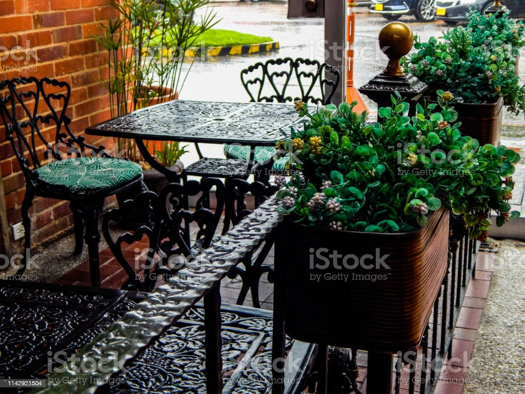 https www istockphoto com photo table and chairs of a restaurant with railing and flowerpots in foreground gm1142921504 306746495