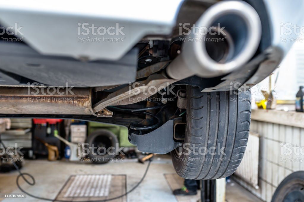 the exhaust system in the car seen from below the car is on the lift in the car workshop stock photo download image now istock