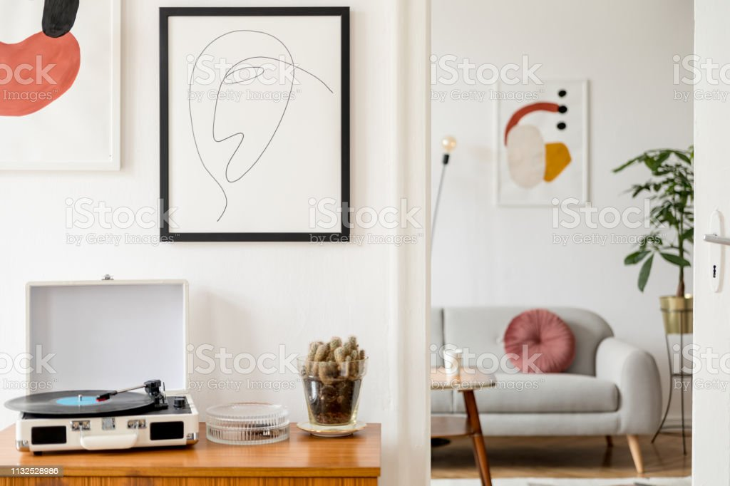 vintage and retro interior of living room with design commode vinyl recorder cacti and mock up posters frames on the white walls cozy room with brown wooden parquet and plants stock photo