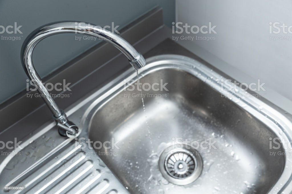 water tap long reach faucet with water drop leak at sink basin to waste water stock photo download image now istock