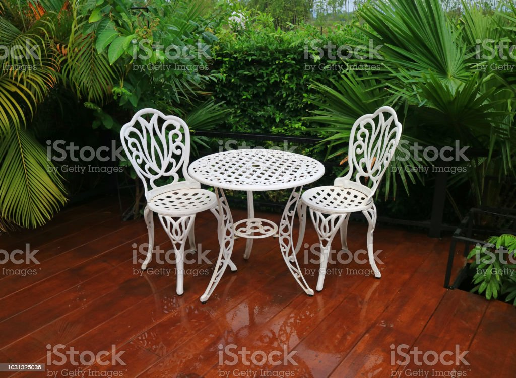 white colored wrought iron table and chairs in green garden terrace after the rain stock photo download image now istock