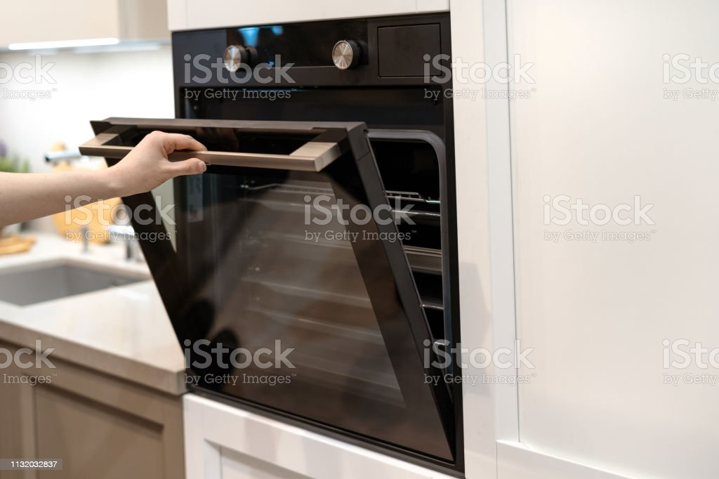 woman hand opening door of new modern builtin oven in white kitchen cabinet stock photo download image now istock