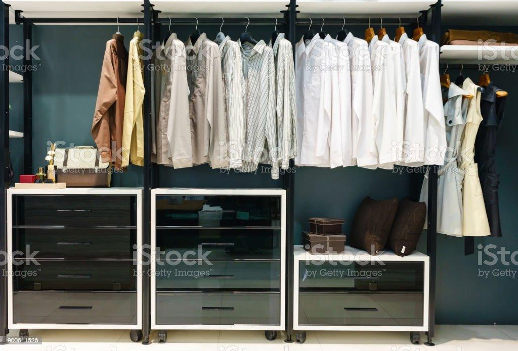https www istockphoto com fr photo armoire en bois dans le dressing avec des v c3 aatements suspendus sur rail le concept de gm900611526 248476973