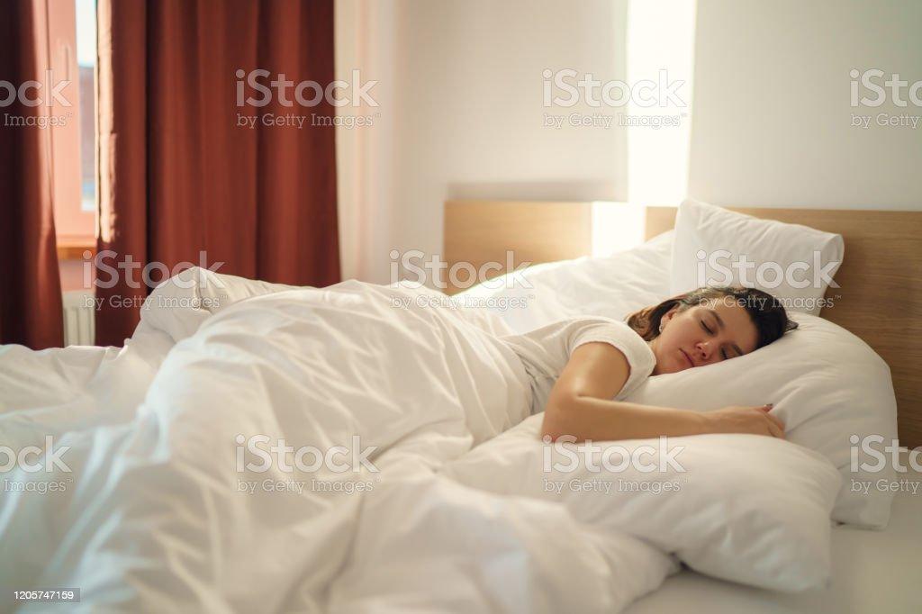 https www istockphoto com fr photo jeune belle femme seule dormant sur le lit dans la chambre c3 a0 coucher gm1205747159 347461316