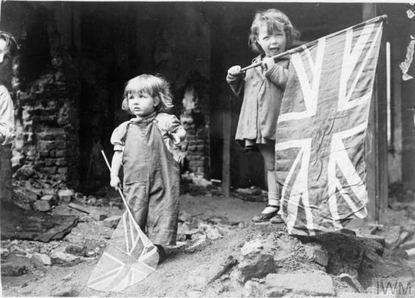 Two small girls waving their flags in the rubble of Battersea, snapped by an anonymous American photographer.