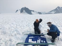 Students Stacey Edmonsond (left) and Audrey Erickson (right) of the Juneau Icefield Research Program, measure glacier mass balance at the flow divide of Taku and Mendenhall glaciers during the summer of 2019. (Photo courtesy of Christopher McNeil/USGS)
