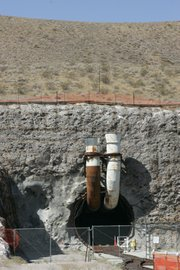 One thousand feet underneath Yucca Mountain is the horseshoe-shaped tunnel into which waste would be carried for disposal, should the Energy Department's plan for the dump be approved. Ventilation pipes jut out from its portals.