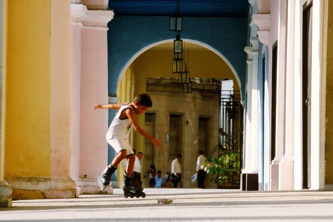Boy rollerblading in arcade of Plaza Vieja, Habana Vieja.