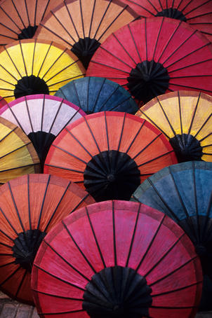 Lacquered umbrellas for sale at evening street market.