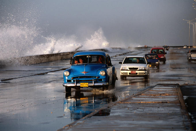 Cars negotiating wet conditions along the Malecon as huge hurricane-powered waves crash over sea wall. Havana, Cuba.