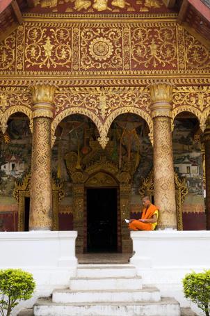 Monk studying on wall of Wat Sensoukharam.